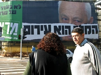 Israelis wait to cross a Tel Aviv street Dec. 30, across from a huge campaign poster denouncing Prime Minister Ariel Sharon. (Brian Hendler)