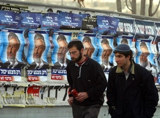 Two seminary students walk past campaign posters for the Labor Party´s Amram Mitzna, in Jerusalem on Jan. 13. (Brian Hendler)