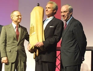 Reform Jewish leaders Rabbi Eric Yoffie, right, and Rabbi David Saperstein, left, look on as former Rep. Joseph Kennedy holds a Torah scroll returned to the movement at the group´s recent biennial in Boston. The Torah was presented by the Reform mov (Michael Fox)