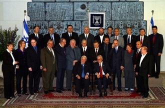 Israeli Prime Minister Ariel Sharon, front left, sits with President Moshe Katsav surrounded by the rest of the new government in Jerusalem on March 3. (Brian Hendler)