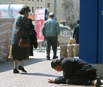An Israeli woman turns to look at a man begging in the street near Jerusalem´s central bus station March 17. (Brian Hendler)