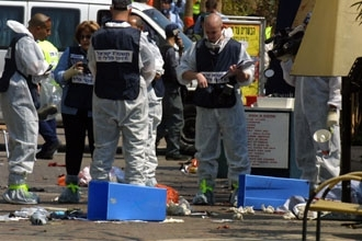 Israeli forensic experts look for evidence at the scene of a suicide bombing outside a cafe in Netanya on March 30.  (BP Images)