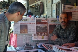 A Palestinian man looks at Arabic newspapers showing Iraqi war scenes, in the Old City of Jerusalem on March 28. (Brian Hendler)