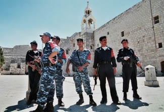 Armed  Palestinian police stand guard near the Church of Nativity in Bethlehem´s Manger Square last year. (Brian Hendler)