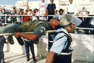 An Israeli policeman wounded by Palestinians on the Temple Mount after Ariel Sharon visited the site is removed in September 2000. (Brian Hendler)