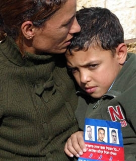 While waiting for the Israeli Cabinet to approve a prisoner swap with Hezbollah, Maatouk Souad, son of First Sgt. Omar Souad, holds a leaflet showing his father, left, and the other kidnapped Israeli soldiers. (Brian Hendler)