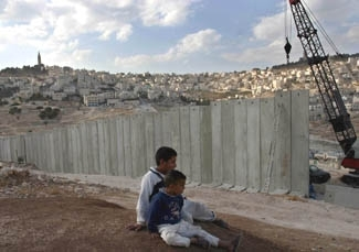 Palestinian brothers Ali Hussein, left, 10, and Ahmed, 7, watch on Nov. 23 as Israel builds a security fence that will cut off their West Bank village, Eizariya, from Jerusalem. (Brian Hendler)