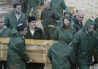 Israeli soldiers carry the exhumed body of one of 59 Lebanese terrorists from the army's Enemy Graveyard, Jan. 26. (BP Images)