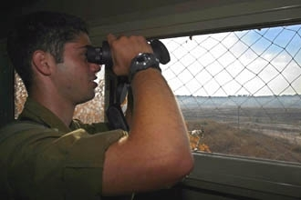 An Israeli soldier watches the fence between the Gaza Strip and Israel at Kissufim army base in July 2003. (Brian Hendler)