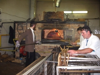 Freshly baked shmura matzah is taken out of the oven and inspected in a  Dnepropetrovsk, Ukraine, factory in December 2003. (Lev Krichevsky)