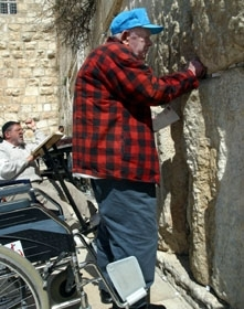 Arthur Rosenberg, 82, leaves his wheel chair to place notes into cracks in Jerusalem´s Western Wall on March 10. (Brian Hendler)