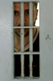 A Palestinian security prisoner peers out of his cell in a maximum security prison north of Tel Aviv in 2003. (Brian Hendler)
