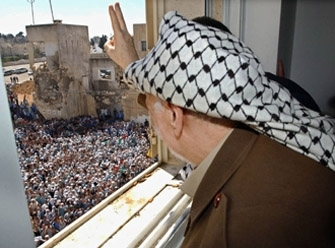 Palestinian leader Yasser Arafat gestures to supporters from his Ramallah headquarters in Sept. 2003. (BP Images)