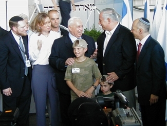 Ariel Sharon, center, and Benjamin Netanyahu, second from right, pose with new immigrants from the U.S. and namesakes, brothers Benjamin, 11, and Ariel Shain, 3, July 14 at Ben Gurion Airport. (Jonathan Udren)