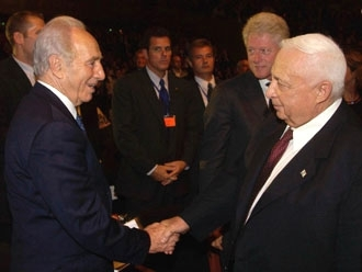 Shimon Peres, left, shakes hands with Ariel Sharon in 2003. (GPO/BP Images)