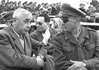 Defense Minister Pinchas Lavon, left, and Chief of Staff Moshe Dayan, right, speak in a 1953 file photo. Shimon Peres is seated behind them. (GPO)