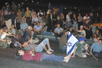 Israelis rest outside the Lion´s Gate during a march around Jerusalem´s Old City after reading from the Book of Lamentations on the eve of Tisha B´Av on July 26, 2004 (Brian Hendler)