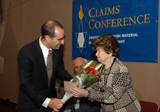 Gideon Taylor gives flowers to Holocaust survivor Gisela Schlanger at a news conference announcing $401 million in payments to former Nazi-era slave and forced laborers, Aug. 2 in New York. (Claims Conference)