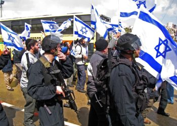 Flag-waving right-wing Israelis, protected by riot police and armored buses, march in the Israeli-Arab city Umm al-Fahm on March 24, 2009. (Brian Hendler)