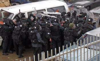 Israeli rot police take cover from stone throwers during a march by right-wing Israelis in the Israeli-Arab city in Umm al-Fahm on March 24, 2009. (Brian Hendler)