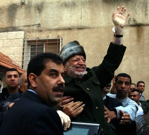 Yasser Arafat waves as he leaves his headquarters in Ramallah, Oct. 29, on his way to Paris for medical treatment. (Hussein Hussein/BP Images)