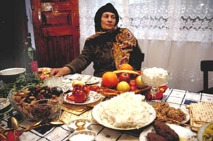Mazanto Agarunov sits at her Pesach feast in Krasnaya Sloboda, Azerbaijan. Mazanto and her contemporaries who grew up in Soviet times are expert Pesach chefs, but remain lost when it comes to the once-prohibited holiday prayers. (Bryan Schwartz)