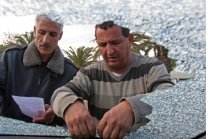 An Israeli clears a shattered window from his car in Ashkelon after a Kassam rocket landed nearby on Dec. 29, 2008. (Brian Hendler)