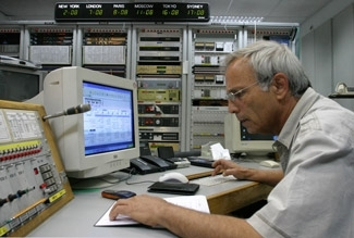 Israeli master riddler Dan Chamizer checks thousands of text messages for correct answers to his riddle during a break in his radio show at the Voice of Israel´s Tel Aviv studios on May 16. (Brian Hendler)