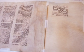 A new parchment page, right, next to the old one from which scribe Neil Yerman copies. (Jane Ulman)
