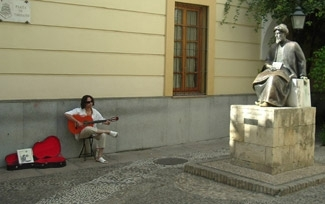 A street musician plays Flamenco guitar next to the statue of the medieval Jewish philosopher Maimonides. (Jerome Socolovsky)