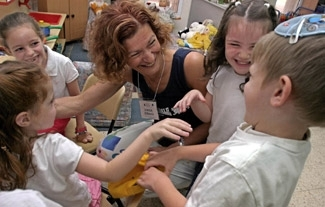 Sharon Spenser, a teacher from Weschester, N.Y., laughs with Israeli students at the Ronit Kindergarten in Jerusalem on June 21. (Brian Hendler)