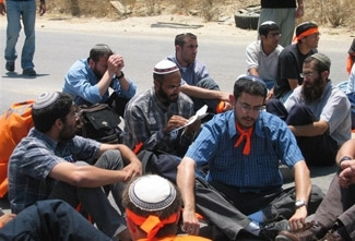 Anti-withdrawal protesters block the road while reciting psalms near the Kissufim crossing into the Gaza Strip on June 30.  (Dina Kraft)