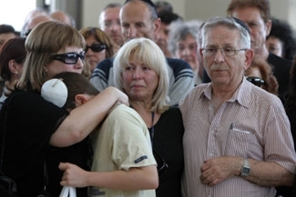Ofrit Ben Menahem, left, sister of London bus bombing victim Anat Rosenberg, comforts her son as they and parents Aryeh, right, and Naomi Rosenberg mourn during her funeral on July 20 in Jerusalem. (Brian Hendler)