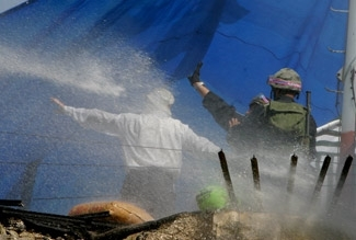 Israeli police use a water cannon against settlers barricaded on the roof of the old British fortress during the pullout from the West Bank settlement of Sa-Nur on Aug. 23. (Brian Hendler)