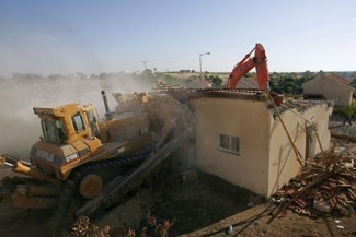 A bulldozer tears through rows of settler homes during the demolition of evacuated settlements on Aug. 21 in the Pe´at Sadeh settlement in the Gaza Strip. (BP Images)