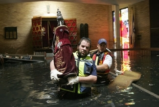 Isaac Leider, a volunteer from ZAKA, carries a Torah out of the flooded Beth Israel synagogue in New Orleans on Sept. 13. (Menahem Kahana/AFP/Getty Images)