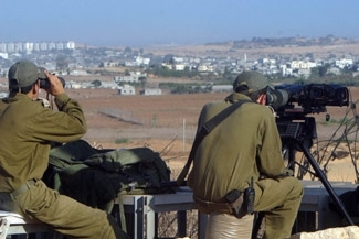 Israeli soldiers watch the Gaza village of Beit Hanoun for Palestinian terrorists trying to launch rockets, from a staging area near Kibbutz Mefallesim, Israel, on Sept. 25. (Brian Hendler)