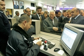 Palestinian Authority President Mahmoud Abbas, center,  waits for his passport to be stamped at the Rafah border crossing terminal on Nov. 25. (Pool/BP Images)