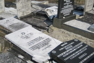 Tombstones damaged by vandals at the Rainsough Cemetery, a Jewish cemetery in Manchester, England, in June 2005. (Courtesy of Community Security Trust )