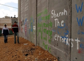 Palestinian boys in the Al Aida refugee camp in the West Bank walk near the Israeli security fence, which is scrawled with graffiti calling Ariel Sharon a ´terrorist,´ on Jan. 9. (Brian Hendler)