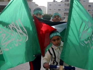 Palestinian children lift Hamas and Palestinian flags near the Central Election Committee buildings in Ramallah, Jan. 24. (Brian Hendler)