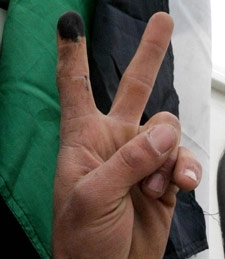 A Palestinian, his finger stained with voting ink, flashes the victory sign on Jan. 25 in the West Bank. (Brian Hendler)