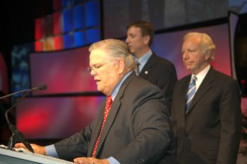 """Pastor John Hagee, with U.S. Sen. Joe Lieberman (I-Conn.) standing behind him, at the Christians United for Israel conference in Washington on July 21, 2009 rapped the Obama administration for """"putting pressure on the wrong people,"""" referring to Israel. (Christians United for Israel)"""