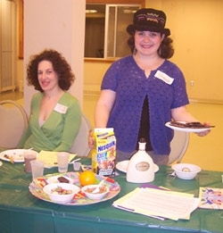 Tracie Bernstein of Beth Am Israel in Penn Valley, Pa., leads a chocolate seder on March 26. Enjoying the feast is congregant Suzanne Comer. (Lisa Hostein)