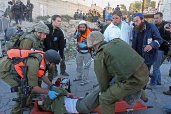 An Israeli border policeman is evacuated after being injured near the disputed Hebron house occupied by right-wing settlers, Dec. 4, 2008. (Brian Hendler)