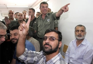Palestinian lawmaker Anwar Zboun, in front, gestures in support of Hamas as he sits with other Palestinian legislators during a hearing in an Israeli military court, July 5. (Brian Hendler)