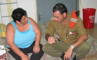 Riki Malka, a Nahariya resident and asthmatic, gets a checkup from an army doctor in the bomb shelter where she has been living for the past three weeks. (Dina Kraft)
