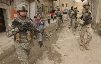 """Soldiers from the U.S. Army patrol the streets of Tall Kayf, Iraq in March, 2006.  (""""Tech. Sgt. John M. Foster, U.S. Air Force/Defense Department"""")"""