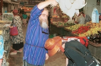 A man swings a chicken over the head of a woman performing the pre-Yom Kippur ritual of kapparot at the Machane Yehuda market in Jerusalem in a file photo. (Brian Hendler)