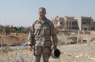 Special agent Lee Mish stands in front of one of Saddam Hussein´s former buildings in Tikrit, Iraq, in the summer of 2004. (Photo courtesy Lee Mish)